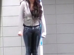 Desperate chick wetting her jeans on the street