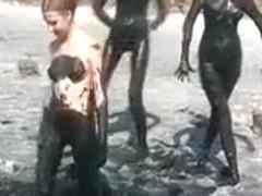 Young ladies coat their bodies in dark mud