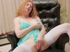 Red haired MILF in a comfy chair and pleasures herself