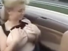 Amateur blonde plays with her huge natural tits in a car