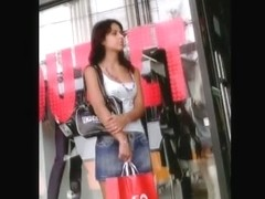 Black hair woman waits on the street while a voyeur films her underskirt ass