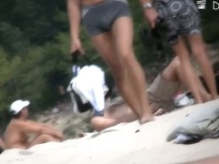 Wonderful babes are sitting on the beach and oiling themselves