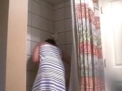 Voyeur tapes a ponytailed brunette girl taking a shower