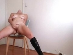 Girl in boots moans loud, as she fingers the clitoris of her shaved pussy.